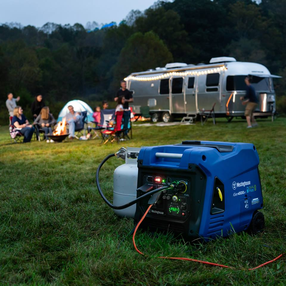 Westinghouse Portable Power Station in foreground with group of people sitting behind it in front of RV. Power station is charging two cell phones sitting on a table.