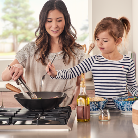 Mom and daughter cooking in kitchen together.