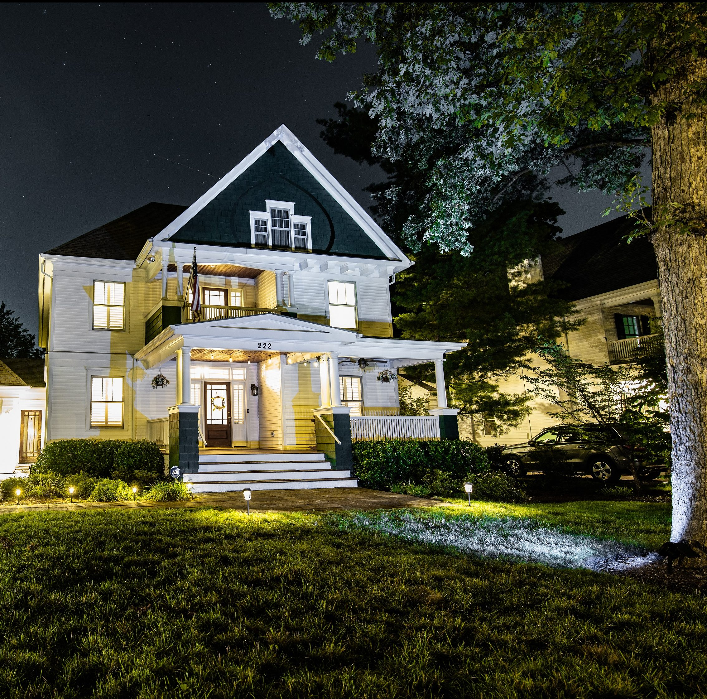 Evening scene of well lit home with solar lighting lining the garden bed in front of the house's porch.